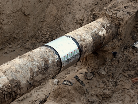 ductile: Excavation pit. Old drink water pipe with stainless repairing sleeve members. Finished repaired piping waiting for covering the clay. Asphalt isolation. Stock Photo