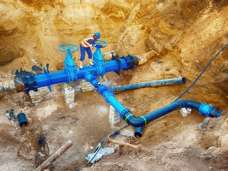 ductile: Technical expert open gate valve on 500 mm joined drink water pipes with new black Waga multi joint members into old pipeline system. Control check of finished piping repaired before covering the clay. Asphalt isolation.