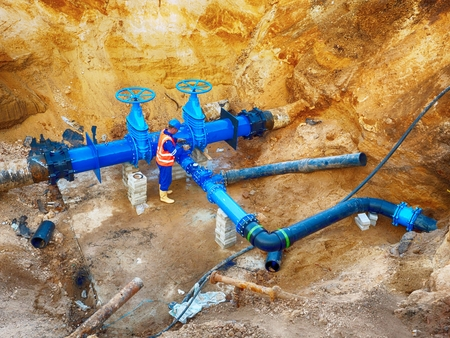 ductile: Technical expert at underground gate valve on 500 mm joined drink water pipes with new black Waga multi joint members into old pipeline system. Check of piping repaired before covering the clay. Asphalt isolation