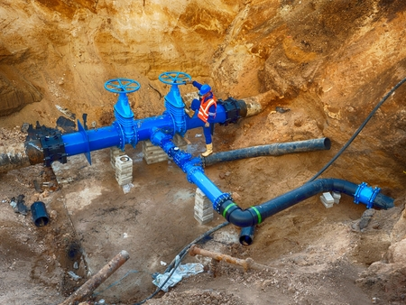 repaired: Technical expert at underground gate valve on 500 mm joined drink water pipes with new black Waga multi joint members into old pipeline system. Check of piping repaired before covering the clay. Asphalt isolation