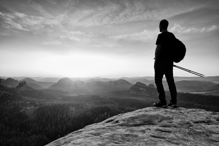 marvelous: Man hiker  at mountain peak. Marvelous daybreak in autumn misty landscape. Sun above horizon. Black and white photo Stock Photo