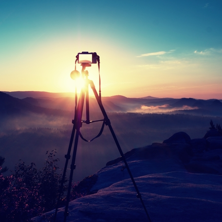 increased: Tripod with running camera on  peak ready for photography. Sharp autumn rocky peaks increased from gold fog. Vivid and strong vignetting effect. Stock Photo