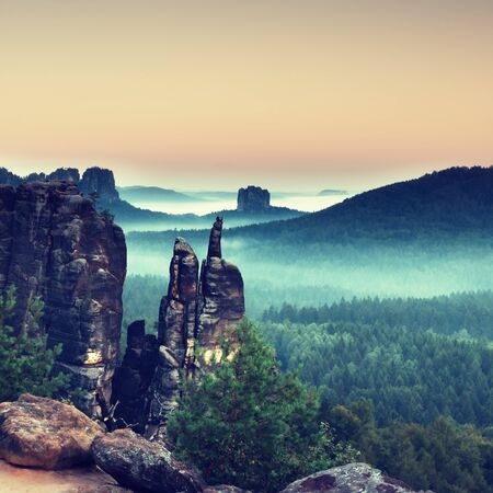 inversion: Autumn evening panorama view over sandstone rocks that fall valley of Saxony Switzerland. Sandstone peaks and hills Increased from colorful background.