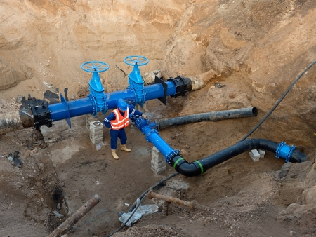 ductile: Technical expert at underground gate valve on 500 mm joined drink water pipes with new black Waga multi joint members into old pipeline system. Repaired piping before covering. Asphalt isolation