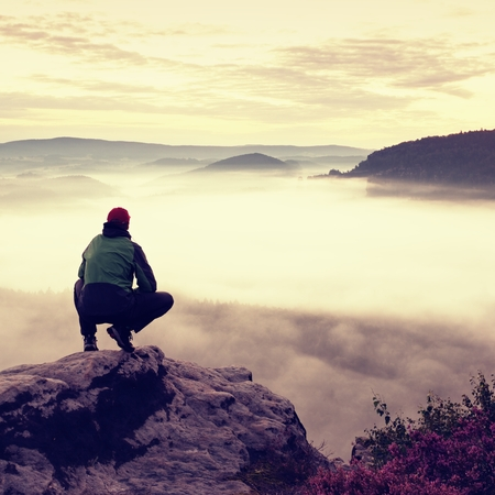 en cuclillas: Turista en la tapa de color rojo y negro en ropa deportiva verde en la posición en cuclillas sobre una roca, disfrutar de un paisaje de otoño