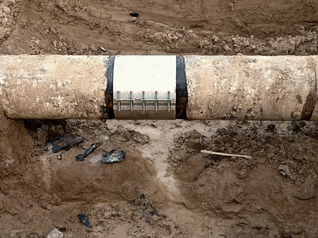 ductile: Old big drink water pipes joined with stainless repairing sleeve members. Finished repaired piping waiting for covering the clay. Asphalt isolation.