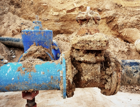 metal corrosion: Detail of fittings, 250mm and 150mm gate valves, reduction joint members in drink water system. Repairing of piping in excavation pit. Extreme kind of corrosion, metal corroded texture. Stock Photo