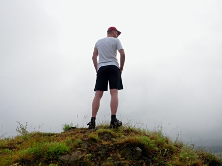 rocky peak: Man in cloud of fog. Hiker in white black sportswear and red cap stand on rocky peak . Around heavy mist. Poor visibility