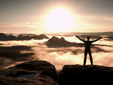 satisfy: Happy man with arms wide open Gesture of triumph. Satisfy Hiker silhouette on sandstone cliff watching down this landscape.
