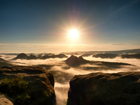 bright orange daybreak. Sandstone cliff above deep misty valley in Saxony Switzerland. Hilly peaks sticking out from creamy fog. Stock Photo