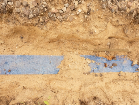 culvert: Trench with blue plastic protection tape. Marked of cables under gravel clay During building of internet connection. Laying underground cable tow.