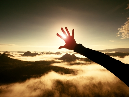 Man hand touch Sun. Misty daybreak in a beautiful hills. Hilly landscape in foggy background, the fog is red and orange due to Sun rays. Lens defects.