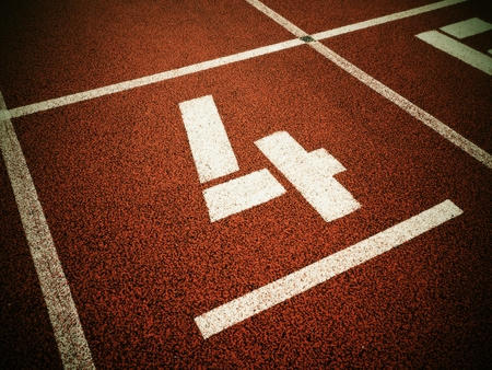 number four: Number four. White track number on red rubber racetrack, texture of running racetracks in stadium Stock Photo