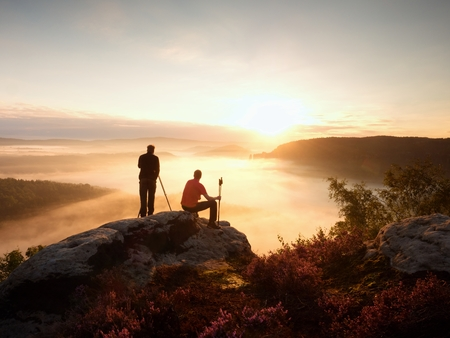 documenting: Hiker and photographer with tripod on rock and takes photos. Dreamy fogy landscape, blue misty sunrise in beautiful valley below Stock Photo