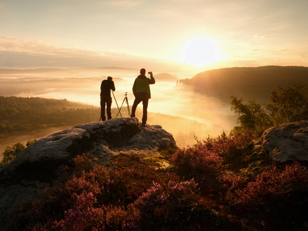 documenting: Photographers stay on cliff and Takes photos. Dreamy landscape fogy, misty orange sunrise in a beautiful valley below