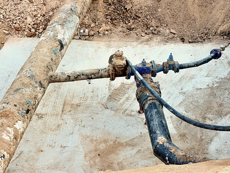 Excavation pit. Old drink water pipe 500 mm with 150 mm arm with cornering gate valves, corroded fittings joining. Tubes repair before piping. Asphalt isolation.