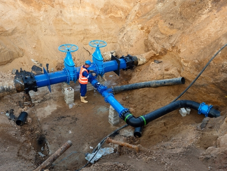 warning vest: Technical expert open gate valve on 500 mm joined drink water pipes with new black Waga multi joint members into old pipeline system. Man control finished piping repaired before covering the clay. Asphalt isolation. Stock Photo