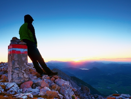 Tired hiker sit on border stone on Alpine mountain. Austria Germany border. Daybreak horizon above blue foggy valley. Mountains increased from humidity