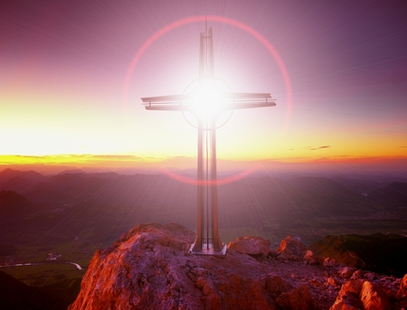 Lens flare light, strong effect. Cross on the peak of Hoher Goell. Iron crucifix at mountain top in the Alps at Austria Germany border. View it Tennen Range and the Dachstein range, Berchtesgaden Alps.