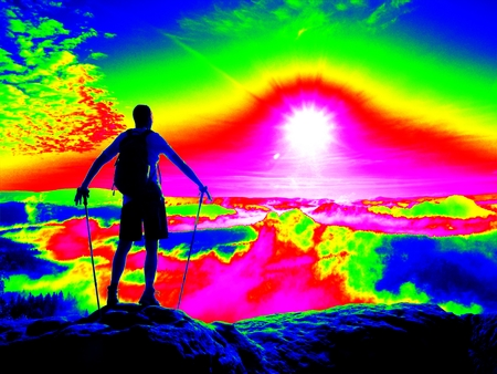 Amazing thermography photo. Hiker with sporty backpack on rocky view point above misty valley