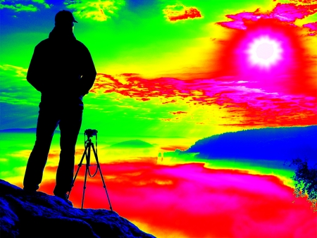 Amazing thermography photo. Photographer  on cliff. Nature photographer takes photos with mirror camera on peak of rock