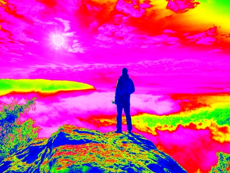 thermography: Amazing thermography photo. Professional photographer with tripod in hands on cliff and thinking. Dreamy fogy landscape Stock Photo