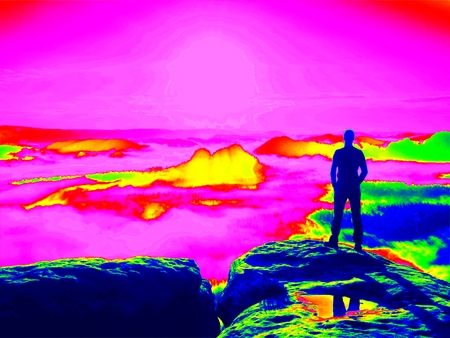 Amazing thermography photo. Tall hiker in black enjoing orange sunrise on view point. Heavy mist bellow in valley. Stock Photo