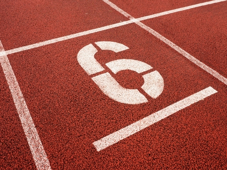 number six: Number six. White athletic track number on red rubber racetrack, texture of running racetracks in stadium