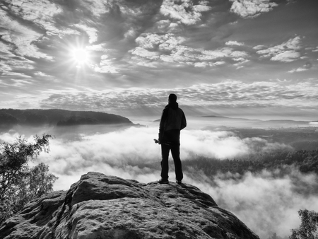 Photographer with folden tripod on end of cliff thinking. Heavy fogy landscape, misty sunrise in  beautiful valley below