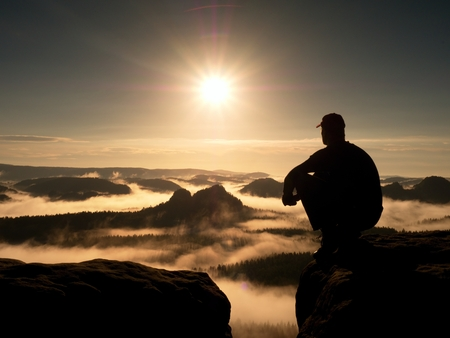 Moment of loneliness. Man with cap sit on the peak of rock and watching into colorful mist and fog in forest valley. Dreamy autumn ladscape