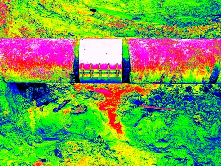 Amazing thermography photo. Excavation pit. Old drink water pipe with  stainless repairing sleeve members. Stock Photo