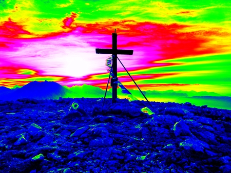 Amazing thermography photo. Big wooden cross at mountain peak in wind with Buddhist praying flags.  Cross on top