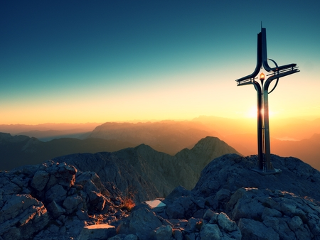 Cross raised  at mountain summit  in Alps. Sharp peak, daybreak Sun in sky. Steel crucifix in memory of victims of mountains. Vivid photo. Stock Photo