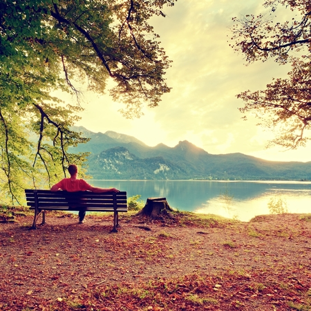 Man sit on wooden bench at mountain lake. Bank under beeches tree, mountains at horizon and in water mirror. Vintage toned photo. Stock Photo