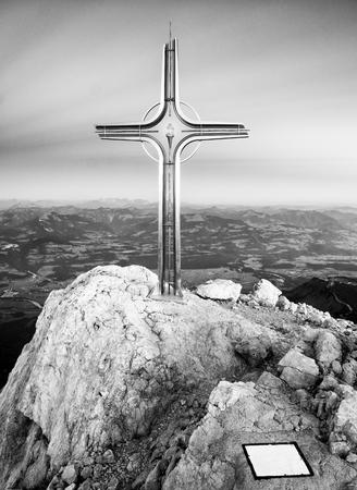 raised viewpoint: Cross raised  at mountain summit  in Alps. Sharp peak, daybreak Sun in sky. Steel crucifix in memory of victims of mountains. Vivid photo. Stock Photo