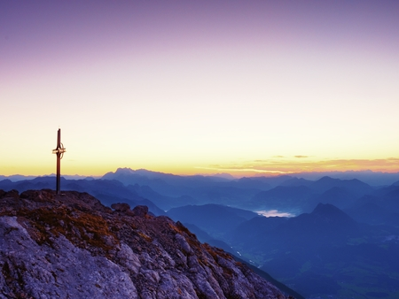Steel crucifix at mountain peak in Alps. Sharp rocky summit, daybreak Sun in sky. Cross raised in memory of victims of mountains. Vivid photo.