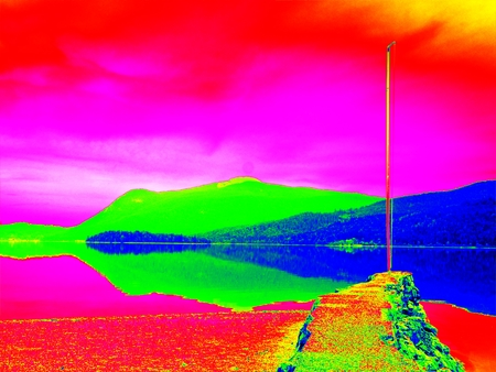 Amazing thermography photo. Stony sporty port at mountain lake. End of wharf with empty pole without flag. Stock Photo