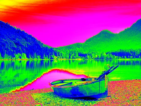 Amazing thermography photo. Abandoned fishing paddle boat on bank of Alps lake. Morning lake glowing by sunlight. Dramatic and picturesque scene.