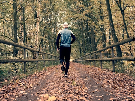 profesional: Sportsman in blue t-shirt and black trousers run on road. The man is Slowly running on asphalt way covered by autumn leaves. Pathway in the park, Beeches and Maples leaves.