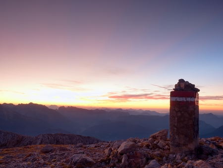 Peak of mountain,  Apine gravel  cliff. Colorful daybreak horizon above blue foggy valley. Mountains increased from humidity