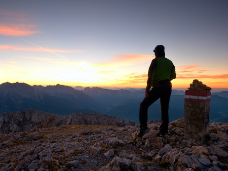 Hiker at peak stone on Alpine mountain. Daybreak horizon above blue foggy valley. Mountains increased from humidity