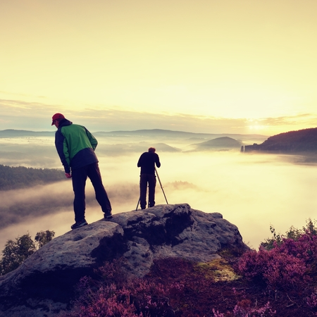 documenting: Hiker look down into fogy valley. Photographer stay on cliff and takes photos. Dreamy fogy landscape, blue misty sunrise in a beautiful valley below Stock Photo