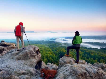 documenting: Hiker and photographer stay with tripod on cliff and takes photos. Autumn windy landscape, misty sunrise in a beautiful valley below Stock Photo