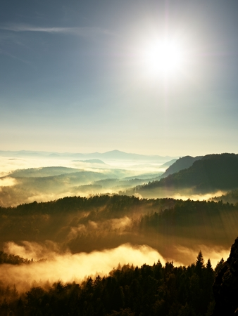 Colorful fall daybreak. Misty awakening in a beautiful hills. Peaks of hills are sticking out from foggy background