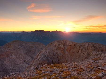 Morning view over Alpine  cliff and valley.Daybreak Sun at horizon. Mountains increased from foggy background