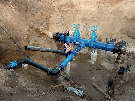 warning vest: Technical expert at underground gate valve on 500 mm joined drink water pipes with new black Waga multi joint members into old pipeline system. Check of piping repaired before covering the clay. Asphalt isolation