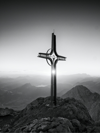 raised viewpoint: Steel crucifix at mountain peak in Alps. Sharp rocky summit, daybreak Sun in sky. Cross raised in memory of victims of mountains. Vivid photo.