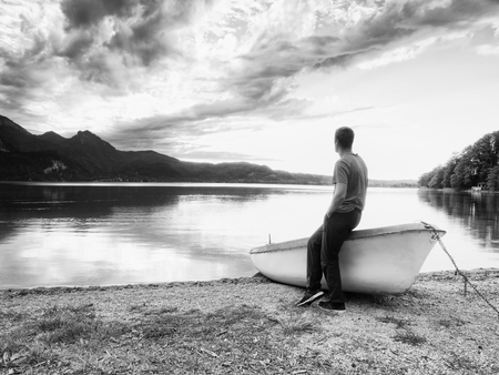 red shirt: Tiired man in red shirt sit on old fishing paddle boat at mountains lake coast. Afternooon sun hidden in clouds above mountain peaks. Vintage photo effect Stock Photo
