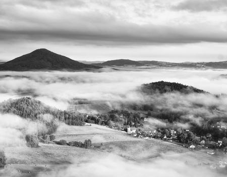 czech switzerland: Alba piena di sole in una bella campagna. Nebbia dolce sopra la chiesa del villaggio. I raggi solari caldi combattono con la nebbia fredda della terra in valle. Foto in bianco e nero