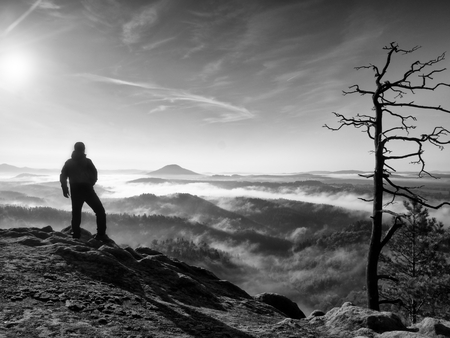 empires: Sunny fall morning. Hiker is standing on the peak of rock in rock empires park and watching over autumn misty and foggy morning valley to Sun. Stock Photo